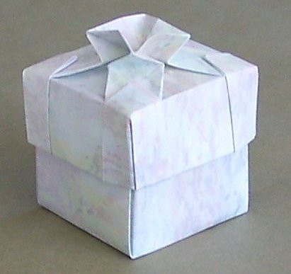 The lid of this box has a design based on the basic tesselation twist.  After forming the design using tesselation techniques the sheet was then treated as a normal square and folded into a basic box shape.  Designed and folded by Rosemary LYNDALL WEMM, 2005