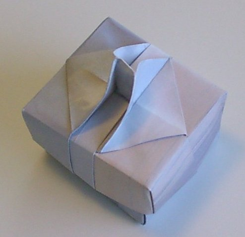 """Handled box. Top view.  Made from 2 pieces of American Letter-sized paper.  This model uses """"designer paper"""".   Design could be modified for A4 paper without too much difficulty.  The handle slot would be wider and the height a little lower.   Designed and folded by Rosemary LYNDALL WEMM, June, 2005"""