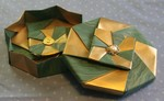 OCTAGONAL GIFT BOX S02  LID: 8 pieces of 10 inch square wallpaper   BASE: 8 pieces of 9 7/8 inch square wallpaper.  Paper is painted gold on the back. Center buttons secured with button safety pins.  VIEW:  Inside of base and outside (top) of lid